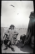 adult male resting in chair on beach 1900s