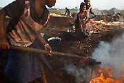 A girl uses a hoe to spread burning charcoal while another splashes it with water to cool it off at a wood charcoal production site on the outskirts of San Pedro, Bas-Sassandra region, Côte d'Ivoire on Sunday March 4, 2012. Men, women and children - who don't go to school - work here seven days a week.