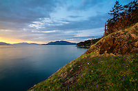 Golden late afternoon light and a beautiifully vibrant colorful sky over Rosario Strait as the sun sets behind Washington's  Decateur and Lopez Islands in the Strait of Juan de Fuca. This view shows Blakely Island to the left and Cypress Island to the right. Photographed from Fidalgo Island in Anacortes.