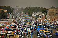 A general view over the Bandim market and the swarming busy crowd along the Airport Avenue. At Bandim you can buy and sell almost anything and a large number of West African vendors with all sorts of merchandise.