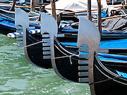 "The decorative fèrro (meaning iron) ornament on the front of gondolas can be made of brass, stainless steel, or aluminum, as counterweight for the gondolier standing near the stern. The six horizontal lines and curved top of the ferro represent Venice's six sestieri (districts) and the Doge's cap. Painting gondolas black originated as a sumptuary law reducing ostentatious competition between nobles. Gondolas are traditional, flat-bottomed Venetian rowing boats which ferry people through the canals. From a peak of ten thousand gondolas in the 1600s and 1700s, just 500 gondolas now ply the Venetian Lagoon. The oar or rèmo is held in an oar lock, or fórcola, shaped for several rowing positions. Until the early 1900s, many gondolas had a small cabin (felze) with windows which could be closed with louvered shutters--the original ""venetian blinds."" The romantic ""City of Canals"" stretches across 117 small islands in the marshy Venetian Lagoon along the Adriatic Sea in northeast Italy, Europe. Venice and the Venetian Lagoons are honored on UNESCO's World Heritage List."
