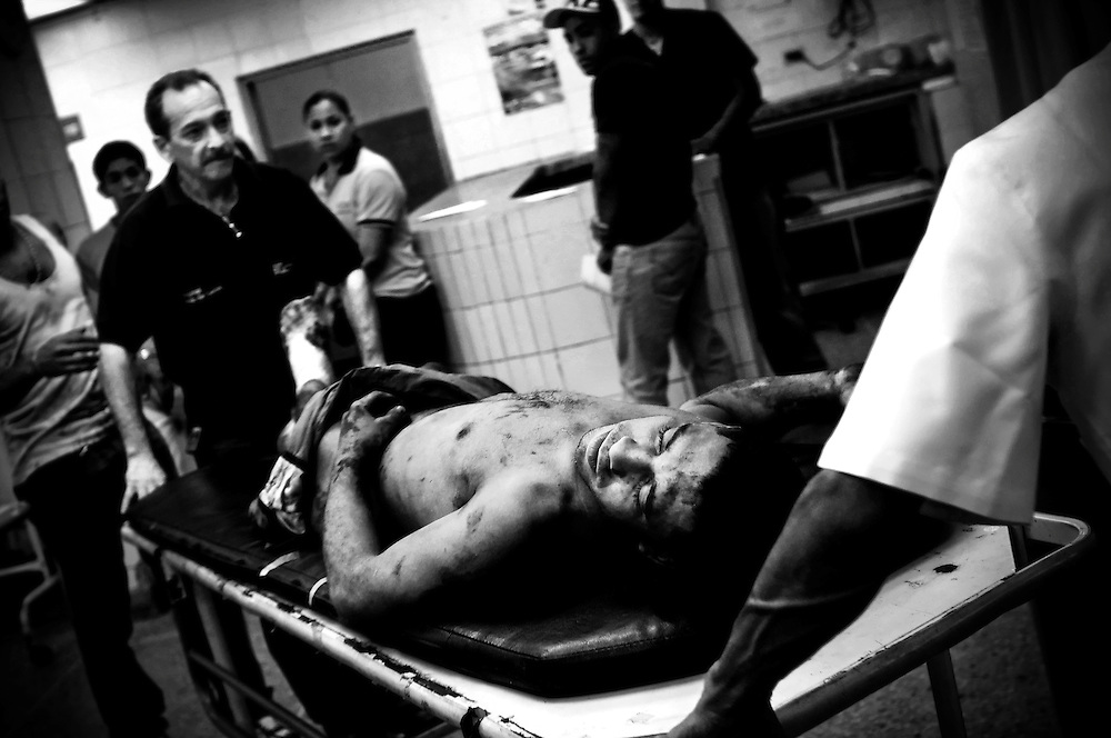 A gun shot victim is brought into the poorly funded and ill equipped Perez Leon hospital emergency room in the Petare slum. The ER, which lacks even the most basic supplies like gauze and IV fluid, receives dozens of gunshot patients every weekend. Trauma surgeon, Dr. Carlos Novel said it feels like he is working in a war zone.