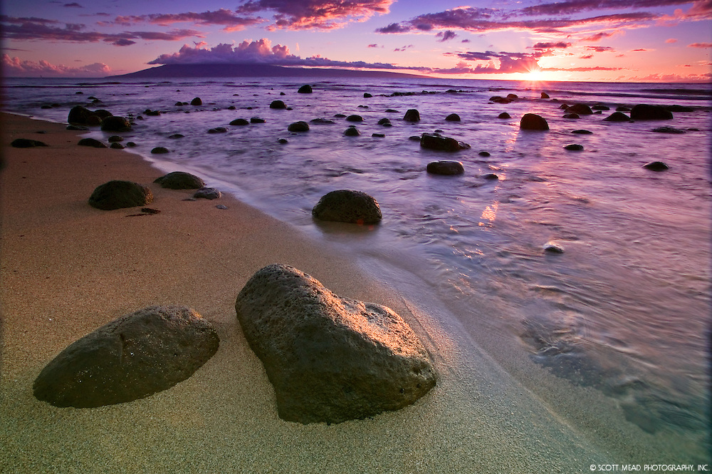 Rocks and ocean along the beach at sunset in Kahana, Maui, Hawaii