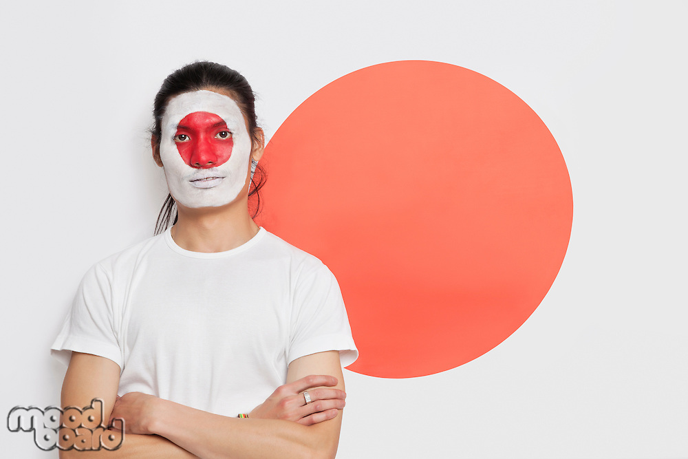 Portrait of young mixed race person with painted face and arms crossed against Japanese flag