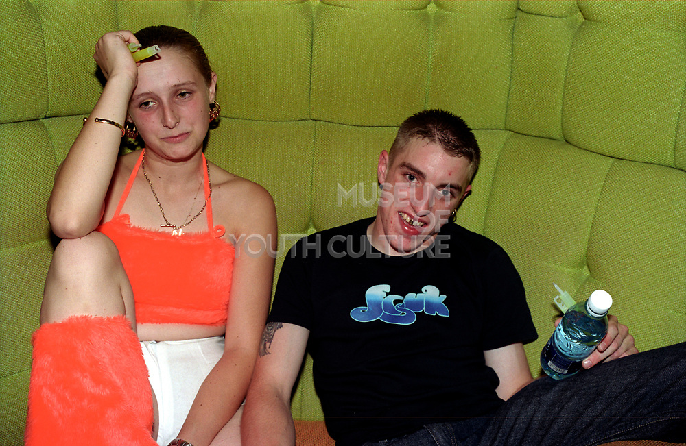 A couple of clubbers sitting on a couch in club Roar, Evolution, Cardiff, Wales, 2001