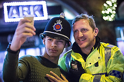 "© Licensed to London News Pictures . 19/12/2015 . Manchester , UK . A man poses for a selfie with a police constable whilst wearing his helmet . Revellers in Manchester enjoy "" Mad Friday "" - also known as "" Black Eye Friday "" - the day on which emergency services in Britain are typically at their busiest , as people head out for parties and drinks to celebrate Christmas . Photo credit : Joel Goodman/LNP"