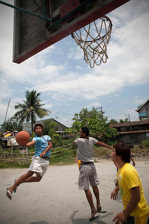 SAN FERNANDO, PHILIPPINES: Kids playing basketball on a street court in San Fernando, Philippines.