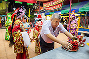 "19 AUGUST 2014 - BANGKOK, THAILAND:  While the patron who sponsored the opera makes an offering, members of the Lehigh Leng Kaitoung Opera troupe pray in the shrine at the beginning of a performance at Chaomae Thapthim Shrine, a small Chinese shrine in a working class neighborhood of Bangkok. The performance was for Ghost Month. Chinese opera was once very popular in Thailand, where it is called ""Ngiew."" It is usually performed in the Teochew language. Millions of Chinese emigrated to Thailand (then Siam) in the 18th and 19th centuries and brought their culture with them. Recently the popularity of ngiew has faded as people turn to performances of opera on DVD or movies. There are still as many 30 Chinese opera troupes left in Bangkok and its environs. They are especially busy during Chinese New Year and Chinese holiday when they travel from Chinese temple to Chinese temple performing on stages they put up in streets near the temple, sometimes sleeping on hammocks they sling under their stage. Most of the Chinese operas from Bangkok travel to Malaysia for Ghost Month, leaving just a few to perform in Bangkok.             PHOTO BY JACK KURTZ"