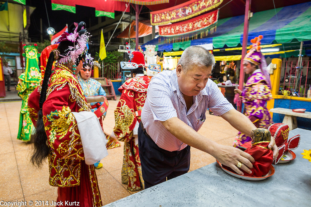 """19 AUGUST 2014 - BANGKOK, THAILAND:  While the patron who sponsored the opera makes an offering, members of the Lehigh Leng Kaitoung Opera troupe pray in the shrine at the beginning of a performance at Chaomae Thapthim Shrine, a small Chinese shrine in a working class neighborhood of Bangkok. The performance was for Ghost Month. Chinese opera was once very popular in Thailand, where it is called """"Ngiew."""" It is usually performed in the Teochew language. Millions of Chinese emigrated to Thailand (then Siam) in the 18th and 19th centuries and brought their culture with them. Recently the popularity of ngiew has faded as people turn to performances of opera on DVD or movies. There are still as many 30 Chinese opera troupes left in Bangkok and its environs. They are especially busy during Chinese New Year and Chinese holiday when they travel from Chinese temple to Chinese temple performing on stages they put up in streets near the temple, sometimes sleeping on hammocks they sling under their stage. Most of the Chinese operas from Bangkok travel to Malaysia for Ghost Month, leaving just a few to perform in Bangkok.             PHOTO BY JACK KURTZ"""