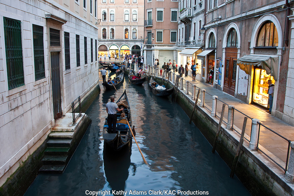 Gondola, gondolier, surrounding streets and crowds, Venice, Italy.