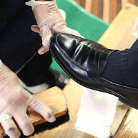 A polishing brush is used to remove the polish from McCain's shoes.
