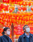 Tourists and locals mask up as they wander the quieter streets of China Town - Anti Coronavirus (Covid 19) defences, wearing inefectual masks in London.