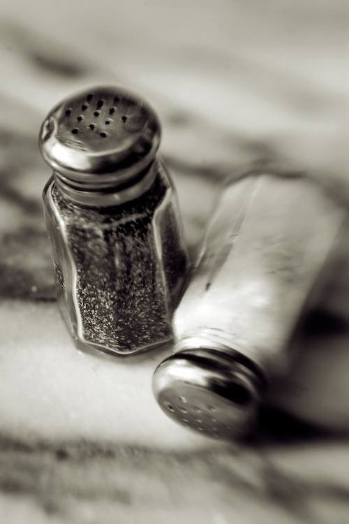 salt and pepper shakers on marble table top,salt spilled,close up,black and white verticle