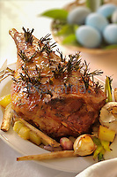 Rosemary and garlic Easter Leg of lamb with roasted garlic, potatoes ans shallots, basket of easter eggs on back