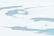 Schmelzwasser-Spuren und auftauender Bergsee bei den Jöriseen oberhalb des Flüela-Passes an einem nebligen und wolkenverhangenen Sommerabend im Juni