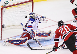 Mar 6; Newark, NJ, USA; New Jersey Devils center Ryan Carter (20) scores a goal on New York Rangers goalie Henrik Lundqvist (30) during the third period at the Prudential Center. The Devils defeated the Rangers 4-1.