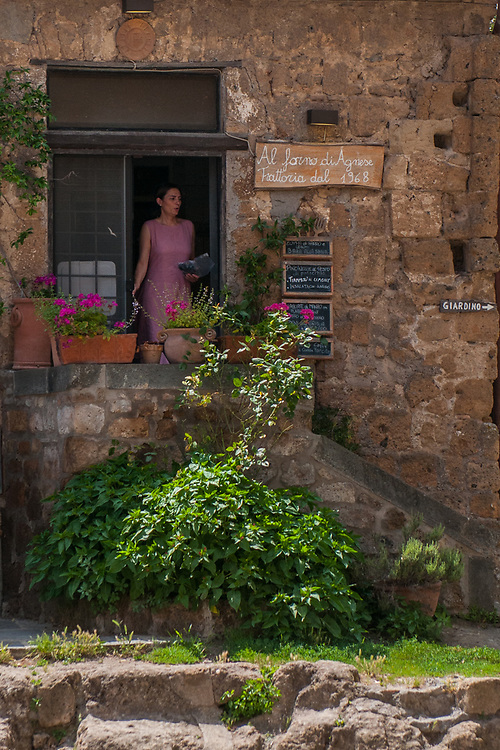 A woman exits from a typical shop in the streets of the village of Civita di Bagnoregio.<br /> Civita di Bagnoregio is a town in the Province of Viterbo in central Italy, a suburb of the comune of Bagnoregio, 1 kilometre (0.6 mi) east from it. It is about 120 kilometres (75 mi) north of Rome. Civita was founded by Etruscans more than 2,500 years ago. Bagnoregio continues as a small but prosperous town, while Civita became known in Italian as La citt&agrave; che muore (&quot;The Dying Town&quot;). Civita has only recently been experiencing a tourist revival. The population today varies from about 7 people in winter to more than 100 in summer.The town was placed on the World Monuments Fund's 2006 Watch List of the 100 Most Endangered Sites, because of threats it faces from erosion and unregulated tourism.
