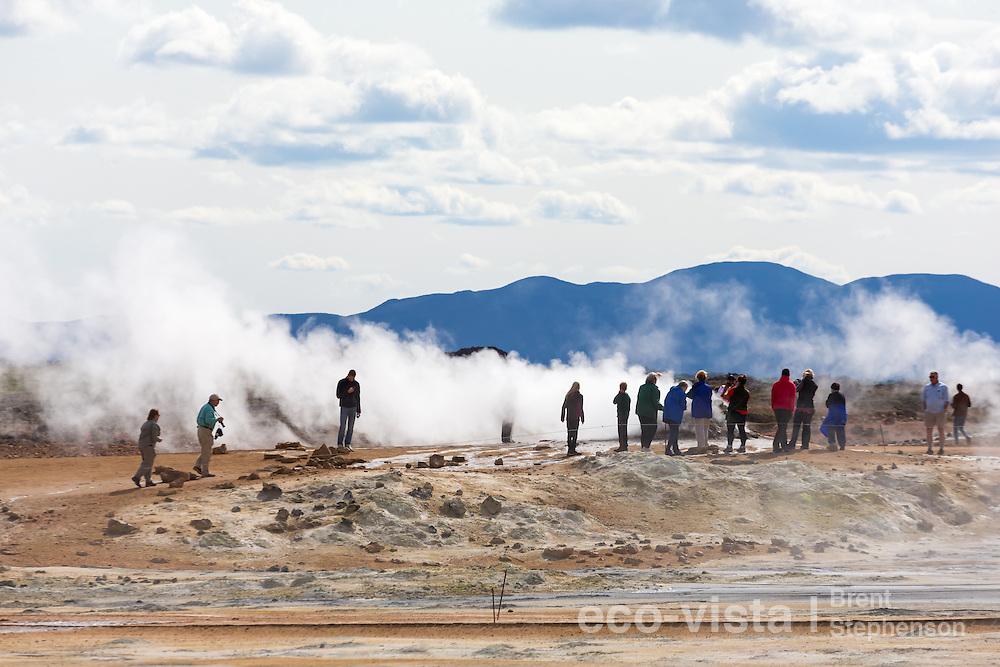People watching the active steam vent blowing steam across the volcanic landscape. Namafjall Geothermal Area, Myvatn, Iceland. July.