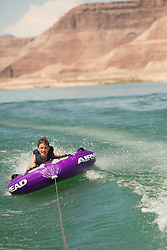 North America, Arizona, Page,  Lake Powell.  Boy (age 12) tubing behind motorboat.  MR