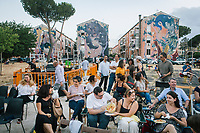"""ROME, ITALY - 27 JUNE 2017: Two people among the audience share pasta salad shortly before the premiere of the """"Don Giovanni OperaCamion"""", an open-air opera performed on a truck in San Basilio, a suburb in Rome, Italy, on June 27th 2017.<br /> <br /> Director Fabio Cherstich's idae of an """"opera truck"""" was conceived as a way of bringing the musical theatre to a new, mixed, non elitist public, and have it perceived as a moment of cultural sharing, intelligent entertainment and no longer as an inaccessible and costly event. The truck becomes a stage that goes from square to square with its orchestra and its company of singers in Rome. <br /> <br /> """"Don Giovanni Opera Camion"""", after """"Don Giovanni"""" by Wolfgang Amadeus Mozart is a new production by the Teatro dell'Opera di Roma, conceived and directed by Fabio Cherstich. Set, videos and costumes by Gianluigi Toccafondo. The Youth Orchestra of the Teatro dell'Opera di Roma is conducted by Carlo Donadio."""