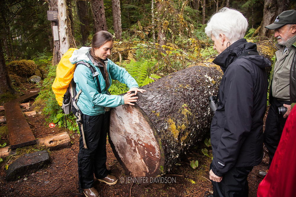 Lindblad-National Geographic Expeditions' Naturalist Emily Mount describes forest ecology to guests from the National Geographic Sea Lion during a hiking excursion along Cascade Creek, Southeast Alaska.