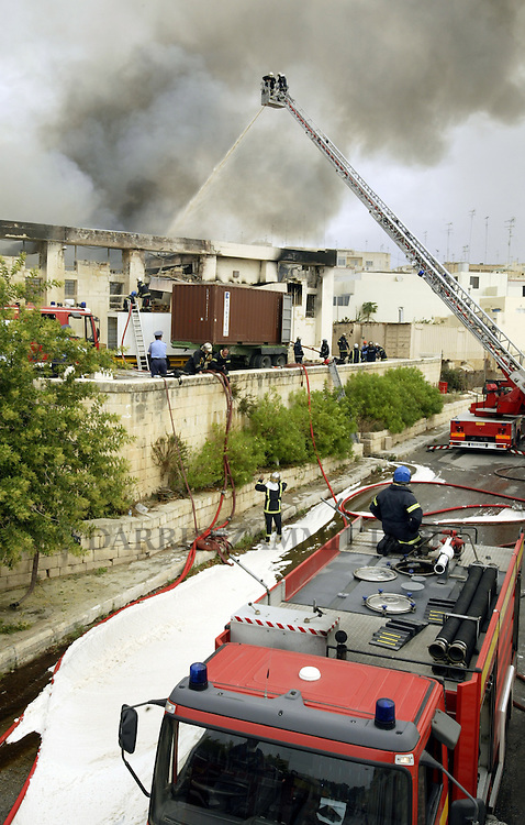 Civil Protection firefighters battle a blaze which gutted two factories at the San Gwann Industrial Estate outside Valletta September 29, 2005.  One worker was injured when the fire broke out in the Trimite paint factory, which quickly spread to a neighbouring screen print factory. Schools in surrounding villages had to be evacuated because of the toxic billowing black smoke, which could be seen from all over the island...MALTA OUT..REUTERS/Darrin Zammit Lupi