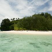 Round island with a white sandy beach.