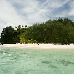Round island with a white sandy beach.