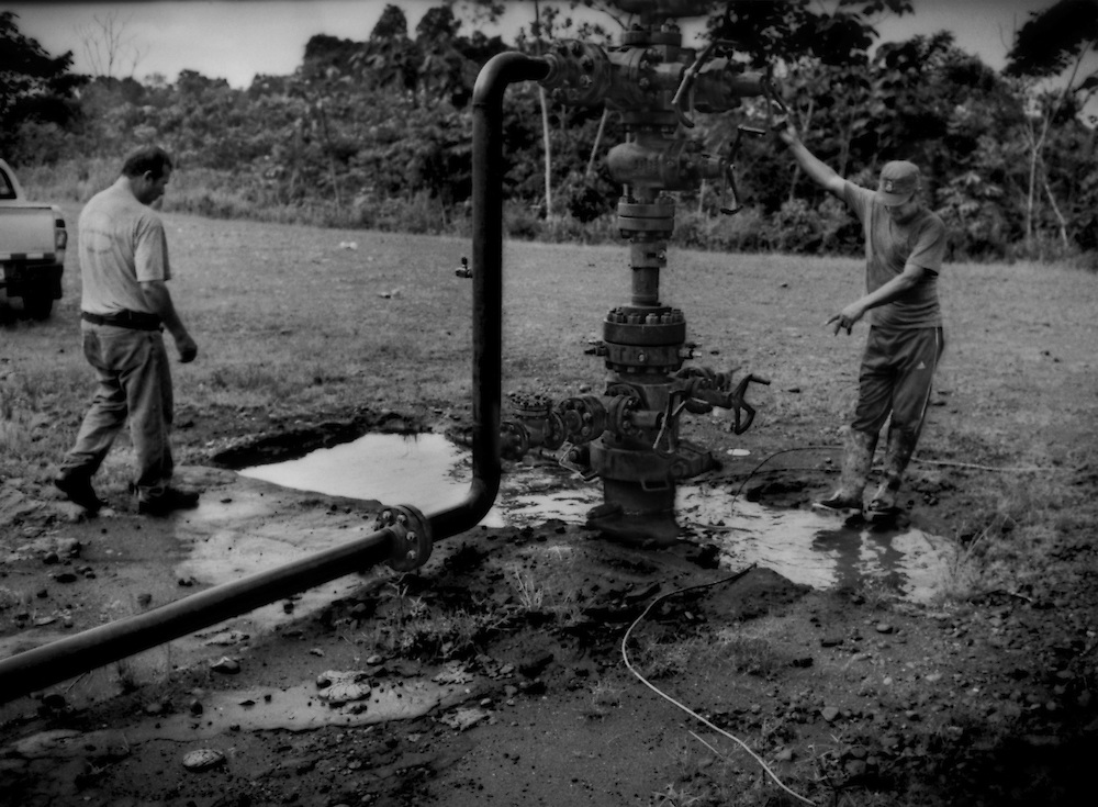 """Afectado (affected person):  Water, highly contaminated by petroleum waste, gathers around a slurry-waste injection compressor inspected by Jose Aveiga, the landowner.  The slurry-waste injection compressor is supposed to safely return waste petroleum slurry safely thousands of meters back into the earth from where the petroleum came at this exhausted well, but it leaks petroleum waste into the environment, where it has soaked into the water table.  Cattle manure can be found around this pit because the cattle drink the contaminated water.  In turn, the family consumes the beef and dairy products from their herd.  Via Auca near the Rio Tiputini, Ecuador. The oil company paid Aveiga US$12/year to occupy this hilltop on his 80 hectare farm.  Via Auca near the Rio Tiputini, Ecuador."