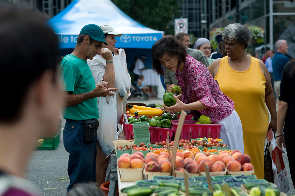 Dick Moran, left, of Harvest Valley Farms, waits while a customer searches for the right green pepper at the Market Square Farmers Market in downtown Pittsburgh.  The market is held every Thursday until November.