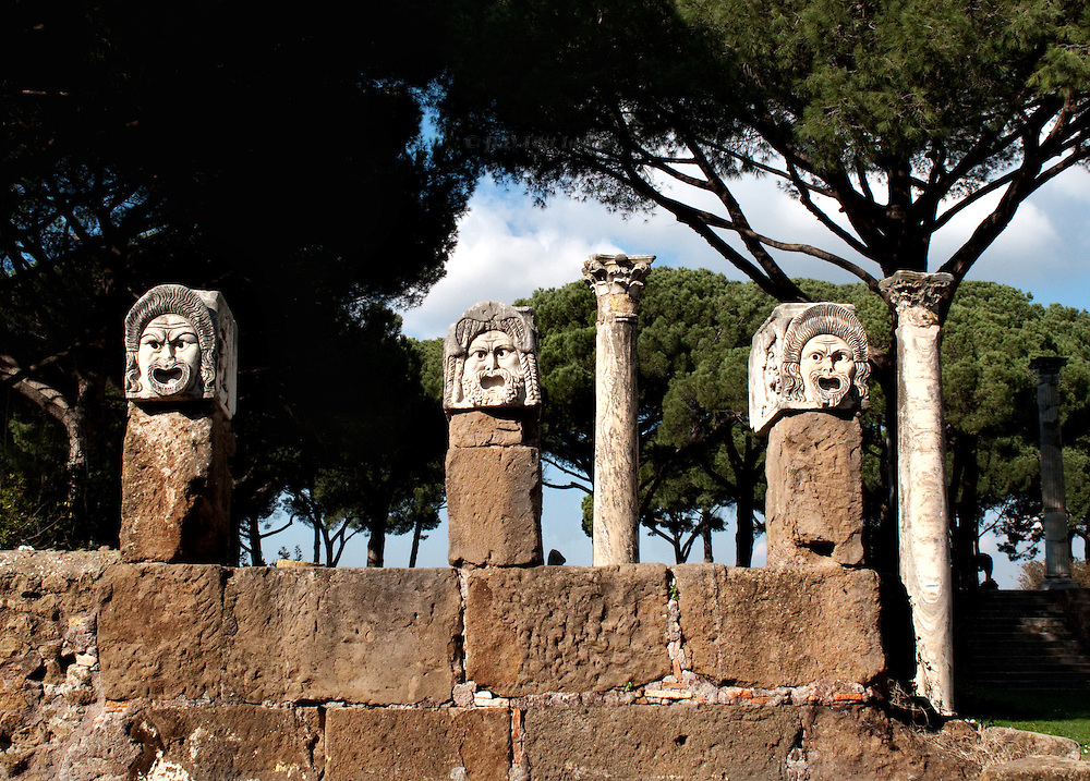 Ostia Antica. Three theatrical masks displayed on short pillars, two columns and umbrella pines behind them.
