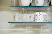 Sad face mug on kitchen shelf