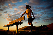A woman stretches against a bench at sunset.