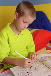 Young boy colouring in picture book using crayon,