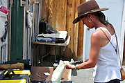 Contest cleaning her revolver at a fast draw contest at Pioneer Day celebration in Idaho City, Idaho