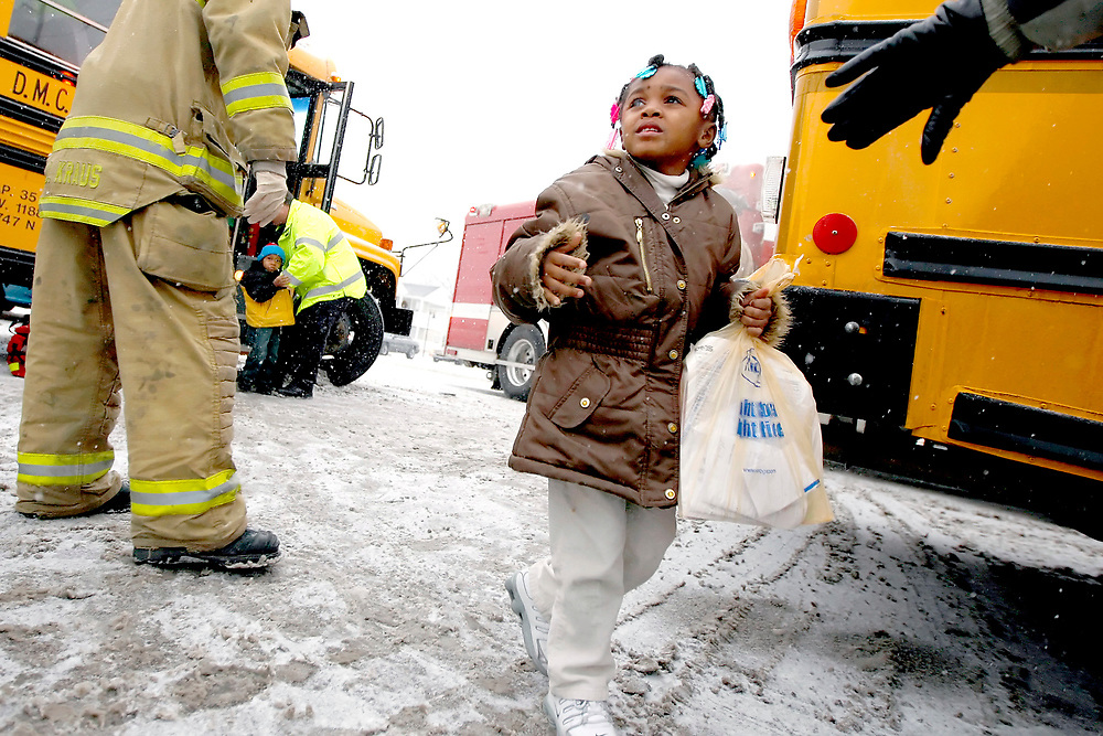 Chyanna Tyus, 5, looks up at her mother, Channie Cook, as emergency personnel move children from one school bus to another after the bus, carrying Tyus and other Anna Waters Head Start students, was involved in a wreck Thursday, Feb. 21, 2008, at the intersection of Martin Luther King, Jr. Drive and Grand Avenue in Decatur, Ill. No one was injured in the crash.
