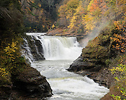 "Lower Genesee Falls. In Letchworth State Park, renowned as the ""Grand Canyon of the East,"" the Genesee River roars northeast through a gorge over three major waterfalls between cliffs as high as 550 feet, surrounded by diverse forests which turn bright fall colors in the last three weeks of October. The large park stretches 17 miles between Portageville and Mount Morris in the state of New York, USA. Drive or hike to many scenic viewpoints along the west side of the gorge. The best walk is along Gorge Trail #1 above Portage Canyon from Lower Genesee Falls (70 ft high), to Inspiration Point, to Middle Genesee Falls (tallest, 107 ft), to Upper Genesee Falls (70 ft high). High above Upper Falls is the railroad trestle of Portageville Bridge, built in 1875, to be replaced 2015-2016. Geologic history: in the Devonian Period (360 to 420 million years ago), sediments from the ancestral Appalachian mountains eroded into an ancient inland sea and became the bedrock (mostly shales with some layers of limestone and sandstone plus marine fossils) now exposed in the gorge. Genesee River Gorge is very young, as it was cut after the last continental glacier diverted the river only 10,000 years ago. The native Seneca people were largely forced out after the American Revolutionary War, as they had been allies of the defeated British. Letchworth's huge campground has 270 generously-spaced electric sites."