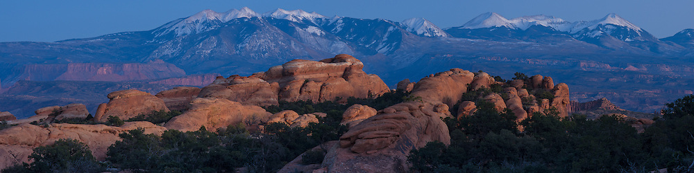 The snowcapped La Sal Mountains form an incredible backdrop for all the red rock formations in Arches National Park. This was taken after sunset while there was still a soft glow in the west to light up these formations known as fins.<br />