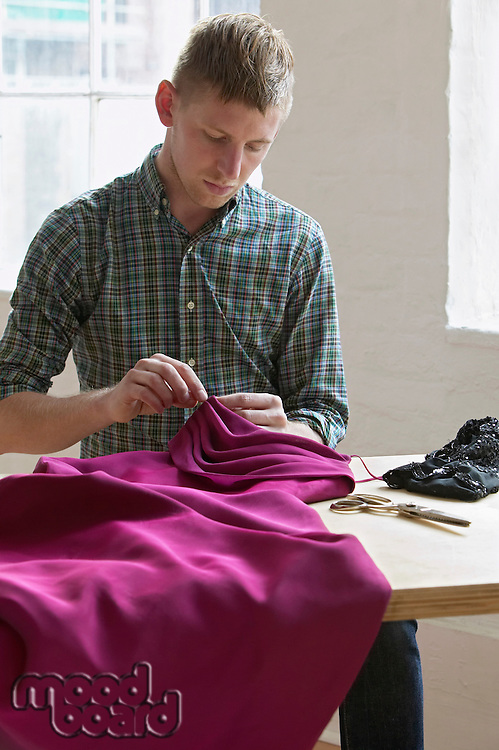 Tailor sewing fabric sitting at table