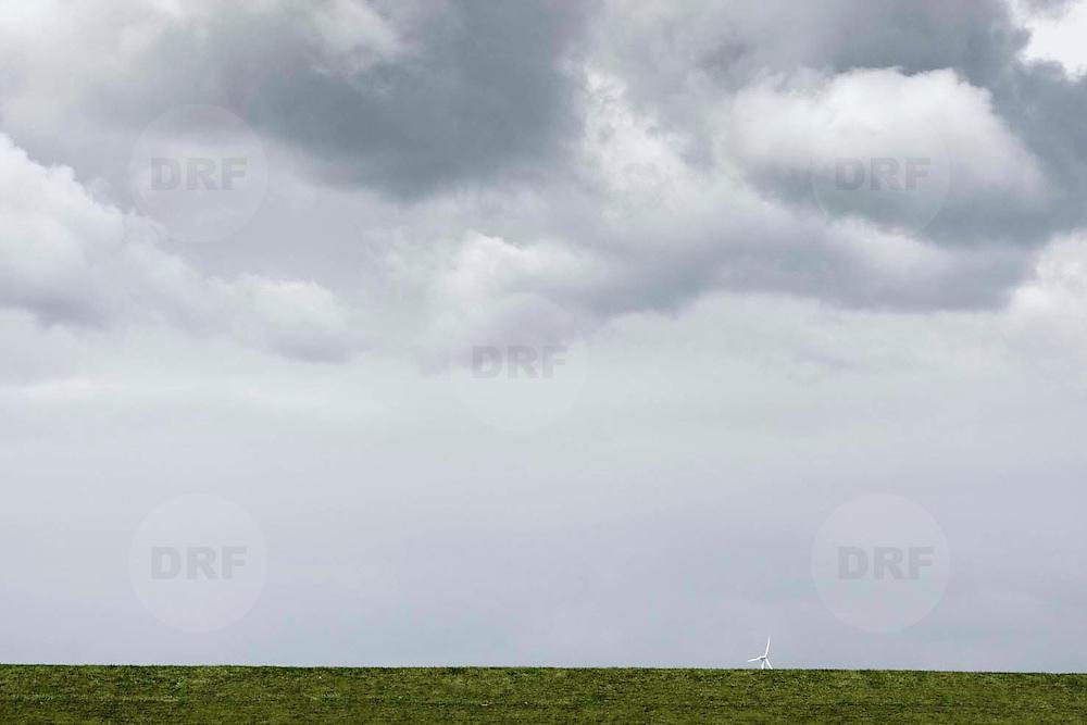 Nederland Coudorpe gemeente Borsele 19 juni 2010 20100619       ..Serie landschappen provincie Zeeland. Zuid Beverland, Polderlandschap, topje van windmolen steekt boven dijk esterschelde. Illustratief beeld schone energie, windenergie. , weiland. Landscape, wijdheid, wijds, wijdsheid, windenergie, windmolen, wit, witte, wolk, wolken, wolkenpartij, zeeland, zeeuws vlaanderen, zeeuws-vlaanderen, zeewering, zo vrij als een vogel, zware, zwitserleven gevoel  ..Foto: David Rozing
