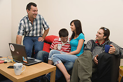 Group of friends in shared house relaxing and chatting,