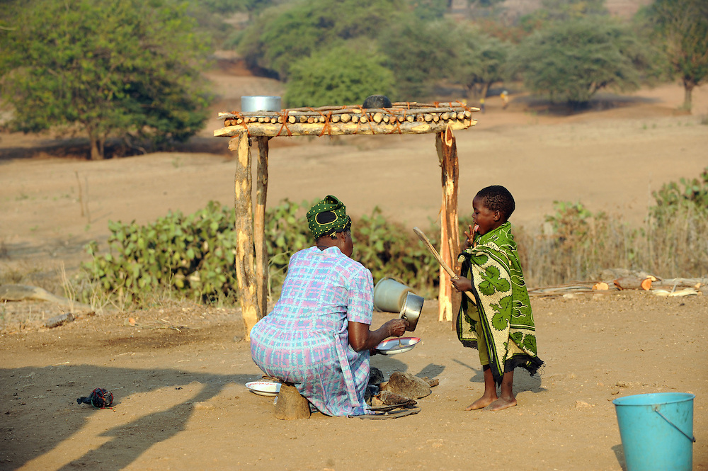 Losista Antonio who lives with her three orphaned grandchildren, (both parents died of AIDS) Felicidade (11), Asis (9) and Evesse (4). Here, Lolista prepares breakfast with Evesse.  Nhabulepule community, Tete province, Mozambique. 29th Augst 2008