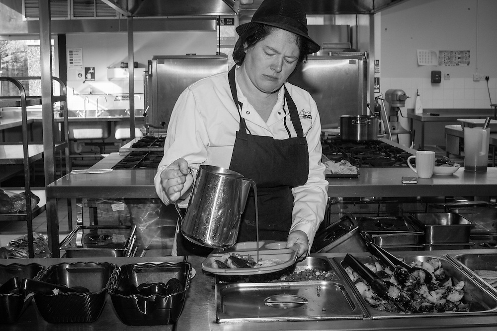 The dinner lady pours gravy on a tray during lunch time at Ben's school in Berkhamsted, England  Wednesday, Feb. 24, 2016 (Elizabeth Dalziel) #thesecretlifeofmothers #bringinguptheboys #dailylife
