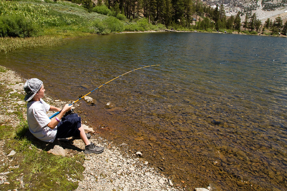 A young man shore fishes at Ellery Lake just outside Yosemite in Lee Vining, CA. This image is model released.