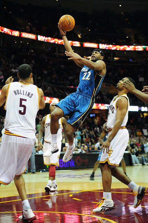 April 13, 2011; Cleveland, OH, USA; Washington Wizards point guard Mustafa Shakur (22) shoots over Cleveland Cavaliers center Ryan Hollins (5) and point guard Ramon Sessions (3) during the fourth quarter at Quicken Loans Arena. The Cavaliers beat the Wizards 100-93. Mandatory Credit: Jason Miller-US PRESSWIRE