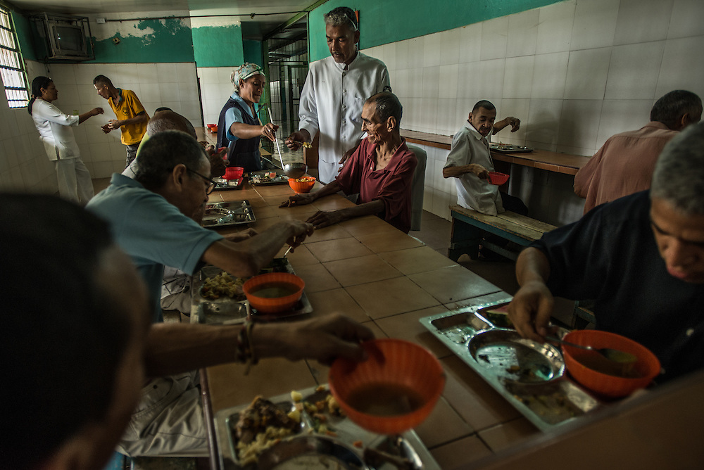 BARQUISIMETO, VENEZUELA - JULY 29, 2016: Patients eat lunch in the men's ward. Over half of male patients at El Pampero are underweight. The economic crisis that has left Venezuela with little hard currency has also severely affected its public health system, crippling hospitals like El Pampero Psychiatric Hospital by leaving it without the resources it needs to take care of patients living there, the majority of whom have been abandoned by their families and rely completely on the state to meet their basic needs. The hospital has not employed a psychiatrist for over two years. The halls are filled with sounds of patients crying or screaming, and an overpowering stench of urine and feces. There is a shortage of food, and drugs used to combat bipolar disorder, epilepsy, schizoaffective disorder and chronic anxiety are now in short supply, as are numerous sedatives and tranquilizers needed to care for patients. PHOTO: Meridith Kohut