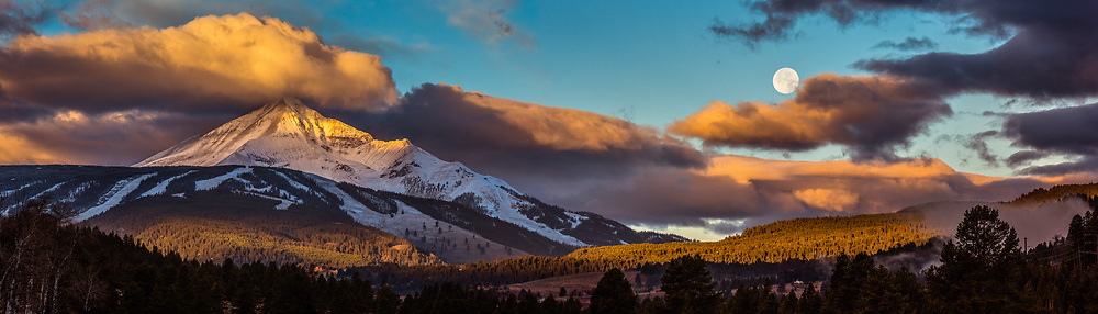 The moon setting on a cool morning in Montana as the sunrises lights up Lone Peak.  Limited Edition - 75