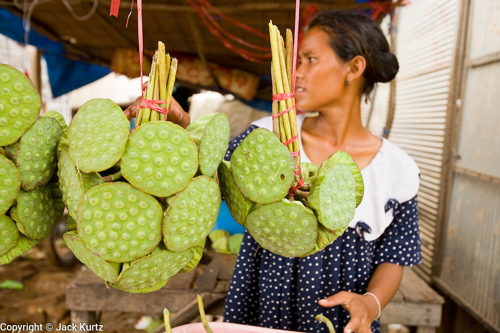 28 JUNE 2006 - SIEM REAP, CAMBODIA: A woman sells lotus buds at a market near Siem Reap, Cambodia. The nuts in the lotus are used as snacks and the flowers are used in Buddhist religious ceremonies. Photo by Jack Kurtz / ZUMA Press