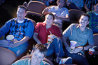 Young men reclining watching movie in theatre smiling