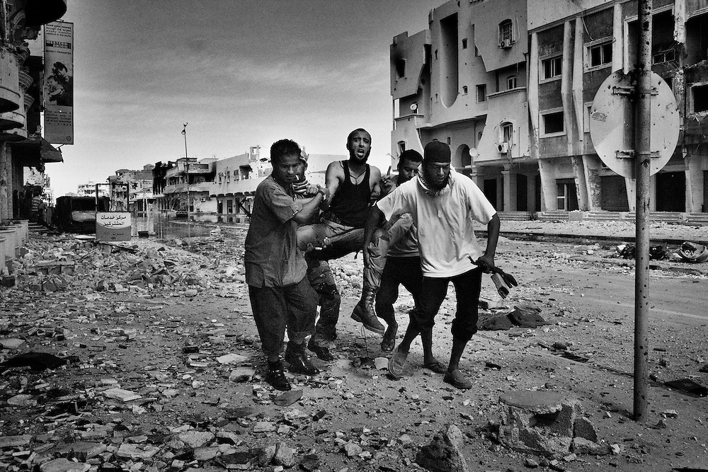 An anti-Gadhafi fighter is carried by comrades after being shot by a sniper during a gunfight against fighters loyal to Col. Moammar Gadhafi in the town of Sirte, Libya, on October 15, 2011. Photo by Mauricio Lima for The New York Times